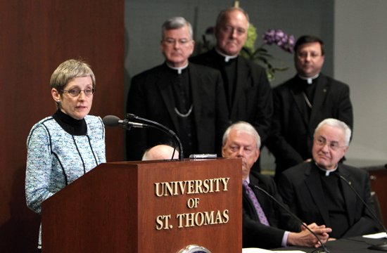 Julie Sullivan delivers remarks during a press conference Feb. 14 where she was announced as the next president of the University of St. Thomas in St. Paul. Listening to her comments are Archbishop John Nienstedt, top row, second from left; Father Kevin McDonough and Bishop Lee Piché. At bottom right is Father Dennis Dease, who will retire as president June 30. Sullivan currently serves as executive vice president and provost of the University of San Diego. She will be the first woman and first lay person to serve as president of UST. (Dave Hrbacek/The Catholic Spirit)