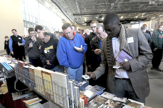 Terry Ndifuanja, right, from St. Peter in North St. Paul, peruses items for sale at the St. George Catholic Books table.