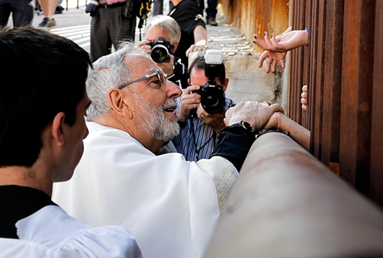 Bishop Gerald Kicanas of Tucson, Ariz., blesses people on the Mexican side as he distributes Communion through the border fence in Nogales, Ariz., April 1. A group of U.S. bishops, led by Cardinal Sean O'Malley of Boston, celebrated Mass at the border calling attention to the plight of migrants and appealing for changes in U.S. immigration policy.  CNS photo/Nancy Wiechec