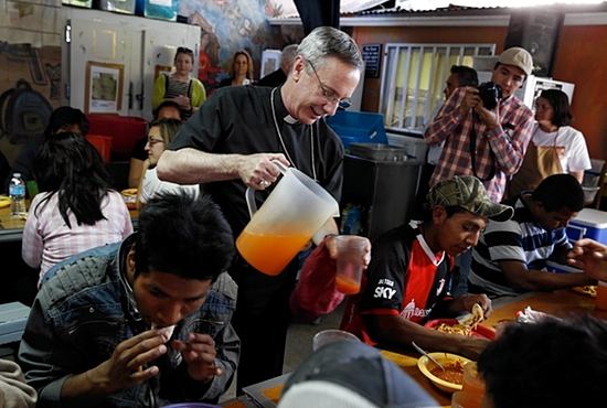 Auxiliary Bishop Luis Zarama of Atlanta serves juice to men at the Aid Center for Deported Migrants in Nogales, Mexico, March 31. Dinner that evening was served by visiting U.S. bishops. The center, run by the Kino Border Initiative, was one stop the bishops made during their tour of the border area near Nogales.  CNS photo/Nancy Wiechec