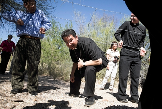 Bishop Oscar Cantu of Las Cruces, N.M., ducks under a barbed wire fence as a group of U.S. bishops tours an area of the Arizona desert north of Nogales March 31.  CNS photo/Nancy Wiechec