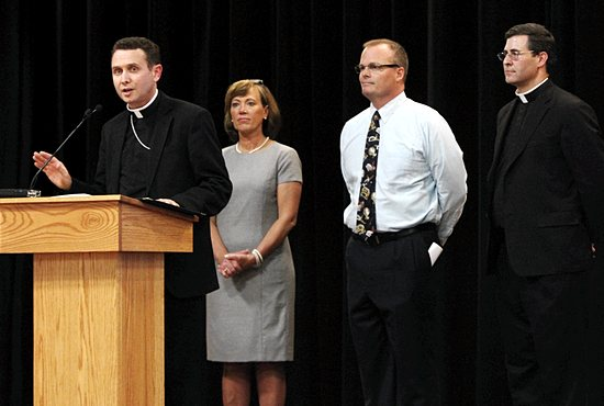 Bishop Andrew Cozzens, left, delivers remarks and a final prayer at an event June 19 announcing a gift of more than $10 million to Saint Agnes School by John Nasseff and his wife, Helene Houle. The money, plus other donations, will be used to  fund a new activities center at the school, which is scheduled to be completed by the fall of 2015. Next to Bishop Cozzens are, from left, Jean Houghton, director of constituent relations, James Morehead, principal, and Father Mark Moriarty, superintendent and pastor of St. Agnes parish.  Dave Hrbacek/The Catholic Spirit