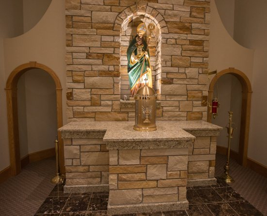 The tabernacle base (front) matches the stone of the wall behind it, both installed by parishioner Dan Cervenka.